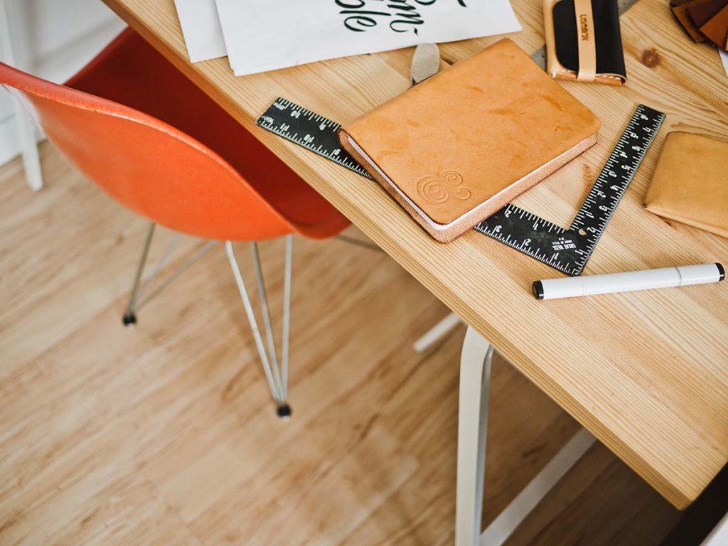 Letisztult tervezőasztal és narancsszínű designerszék látható felülről fényképezve. Az asztalon napló, vonalzó, filctoll, radír és más eszközk láthatóak.
