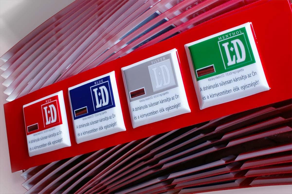 Számtalan vörös vákuumfrmázott displaykorona sorakozik az oldalára fektetve és áegymásba polcolva. Rajtuk hever az egyik külön a kamera felé fordítva, amin jól látszik a négy fehér négyzet, amiben a különböző cigarettaváltozatok színes logói és a figyelmeztetőfelirat jelenik meg.