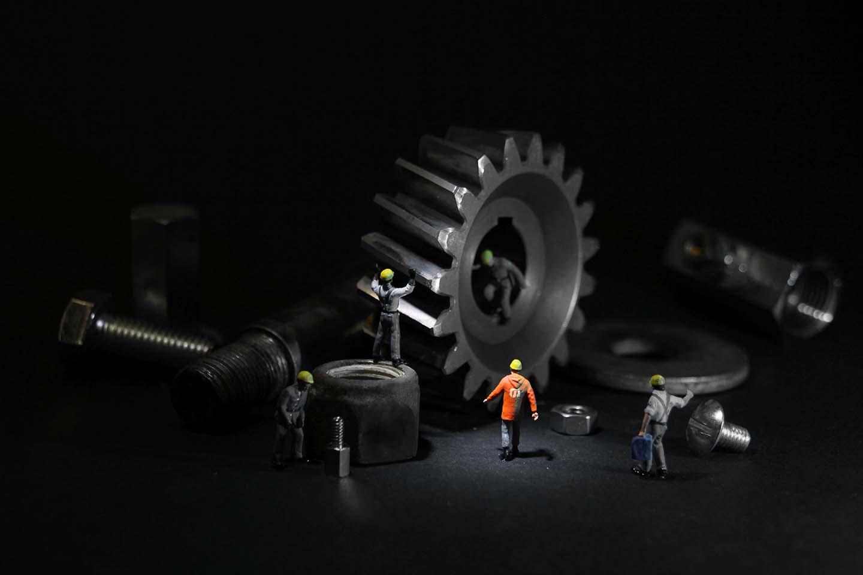 Apró munkások modellfigurái dolgoznak hozzájuk képest hatalmas, valós méretű fém fogaskerekekkel, csavaranyákkal és más alkatrészekkel.