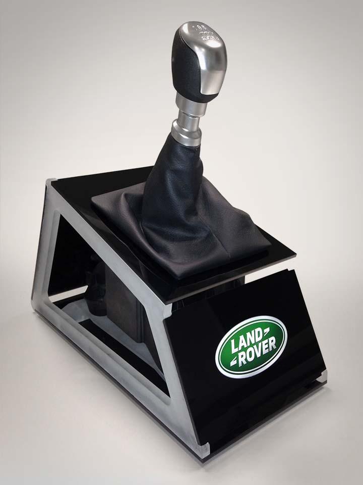 Egy Land Rover váltója elhelyezve egy speciális, áttört oldalú fekete plexitartón, amin ott a Land Rover zöld-fehér emblémája.