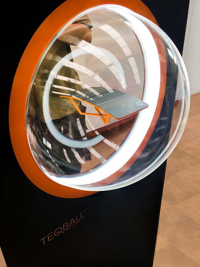 Fekete monolitszerű display, aminek a közepén narancs peremmel egy belülről kivilágított plexigömb van. A gömb közepén lebegni látszik a Teqball kisméretű modellje. Egy férfi fotózza a displayt és a modellt a háttérben.
