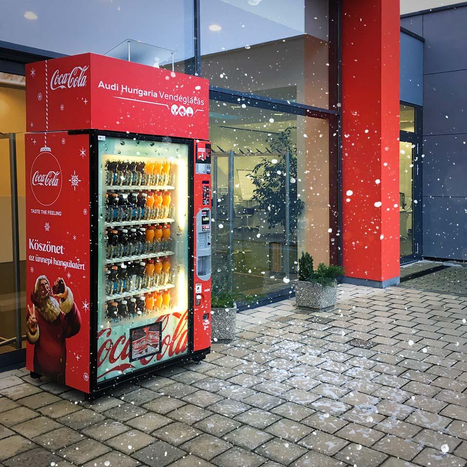 Piros, karácsonyi hangulatban dekorált italautomata áll egy épület előterében. Az uatomata tetején lévő rejtett készülék hóesést imitáló habot fúj magából.
