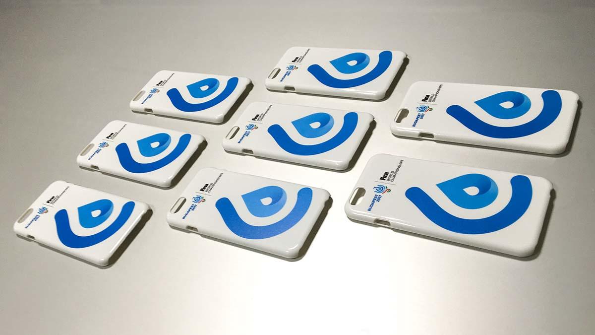 Nyolc darab fehér telefontok fekszik egy ezüst színű aztallaon. Mindegyiken ott a nagyméretű, kék FINA logó.