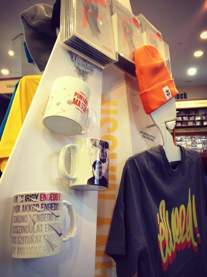 Embermagas papírrepülőt imitáló álló display hajlított plexiből, különböző a zenekarhoz kapcsolódó bögrékkel, pólókkal és füzetekkel tele.