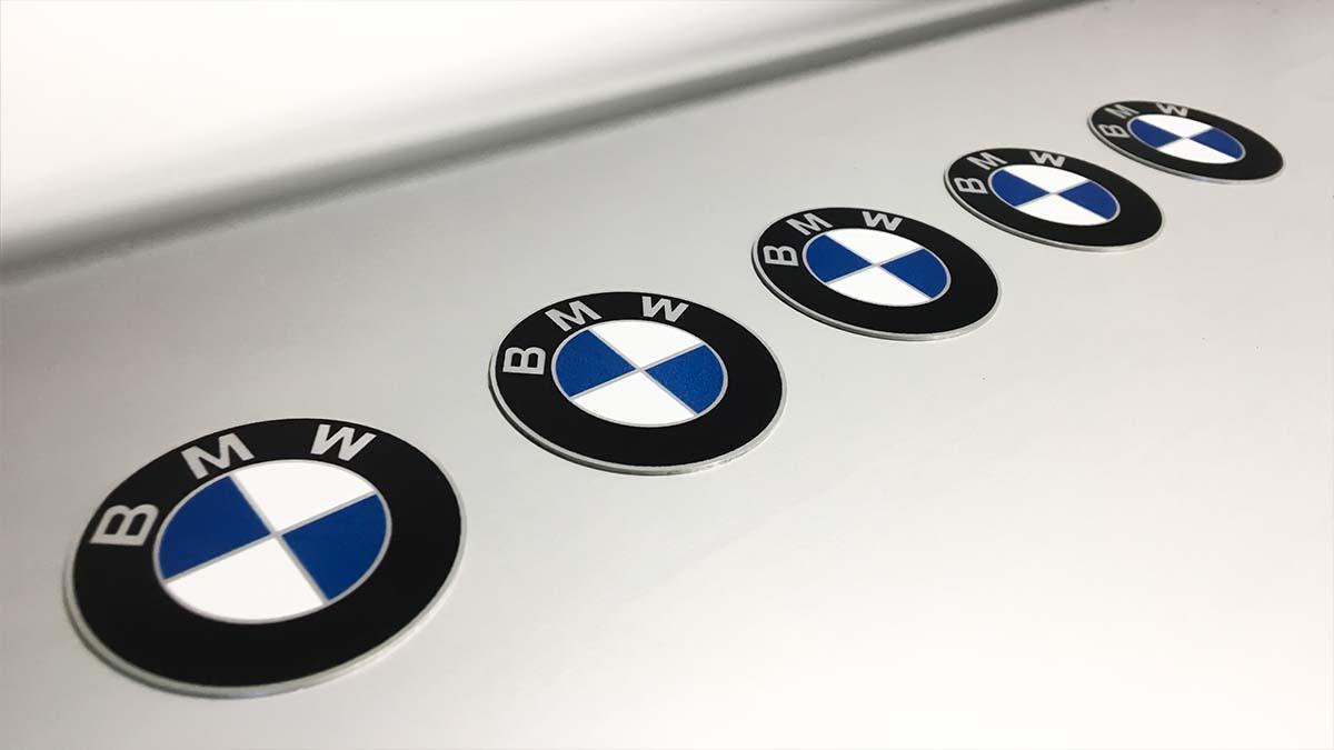 Öt darab egyedi, plexi BMW embléma sorakozik egy szürke posztamensen.