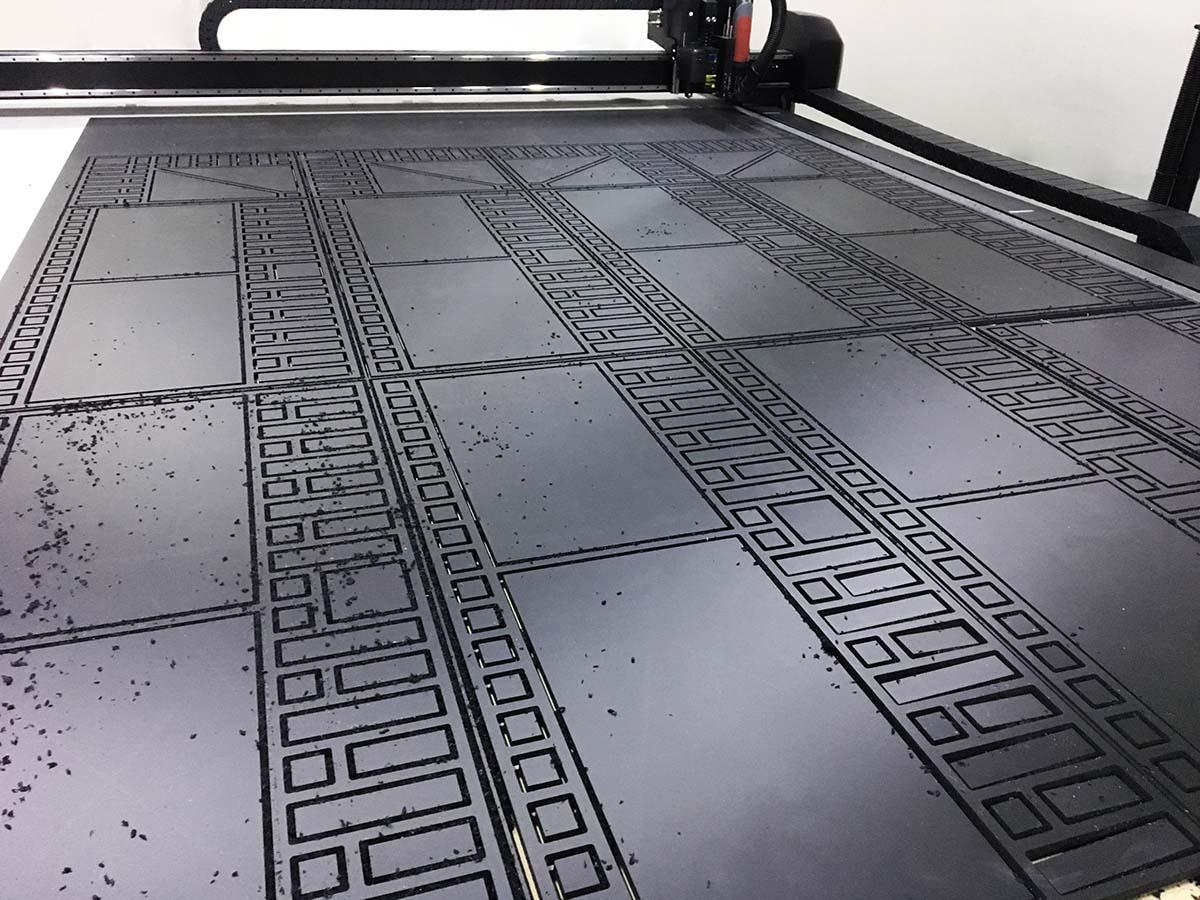 Kivágógép vág ki különböző négyzet és téglalap alakú elemeket egy fekete habosított pvc lemezből.