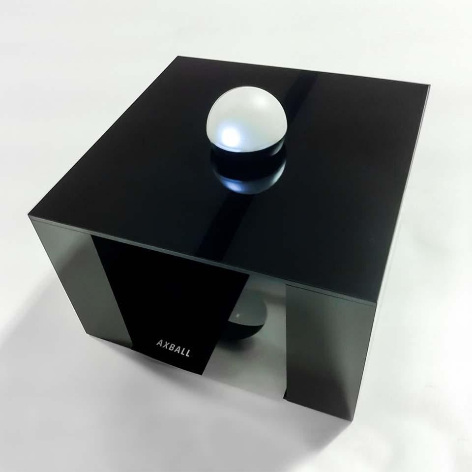 fényes fekete, kockaalakú, alul üreges bemutatóállvány, aminek a tetején ott a kisméretű fehér, gyöngyszerű, félgömb alakú Axball fejlesztsünk.