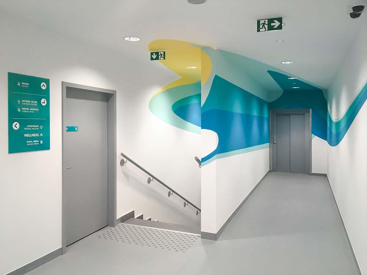 Fhér falú szürke padlójú folyosó és lépcső, szürke lifttel és ajtóval. A falakon a FINA zöldeskék és sárga, hullámotívumokat idéző ornamentikái futnak, az ajtó mellett pedig modern akvamarín színű irányítótáblával.