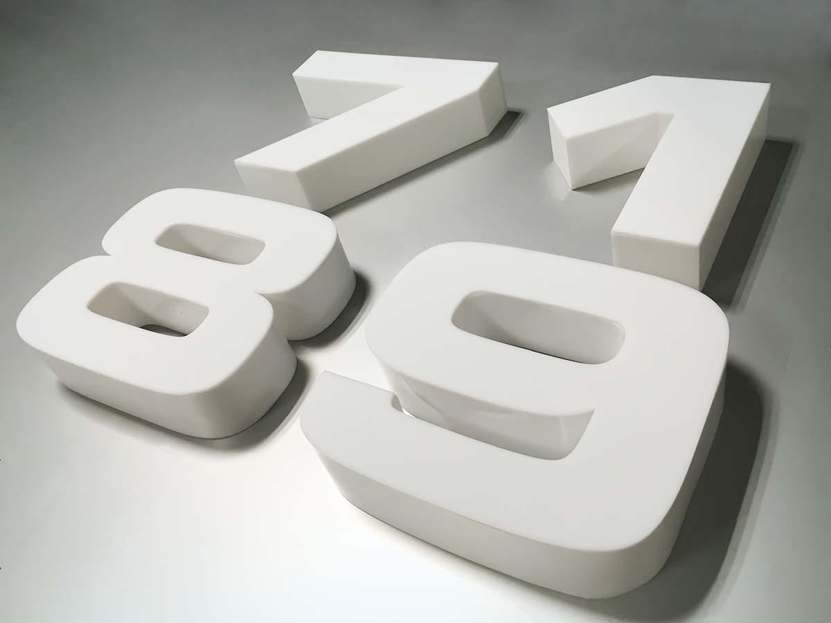 Hatalmas fehér plasztikus 7-es, 1-es, 8-as és 9-es számok fekszenek egy szürke felületen.