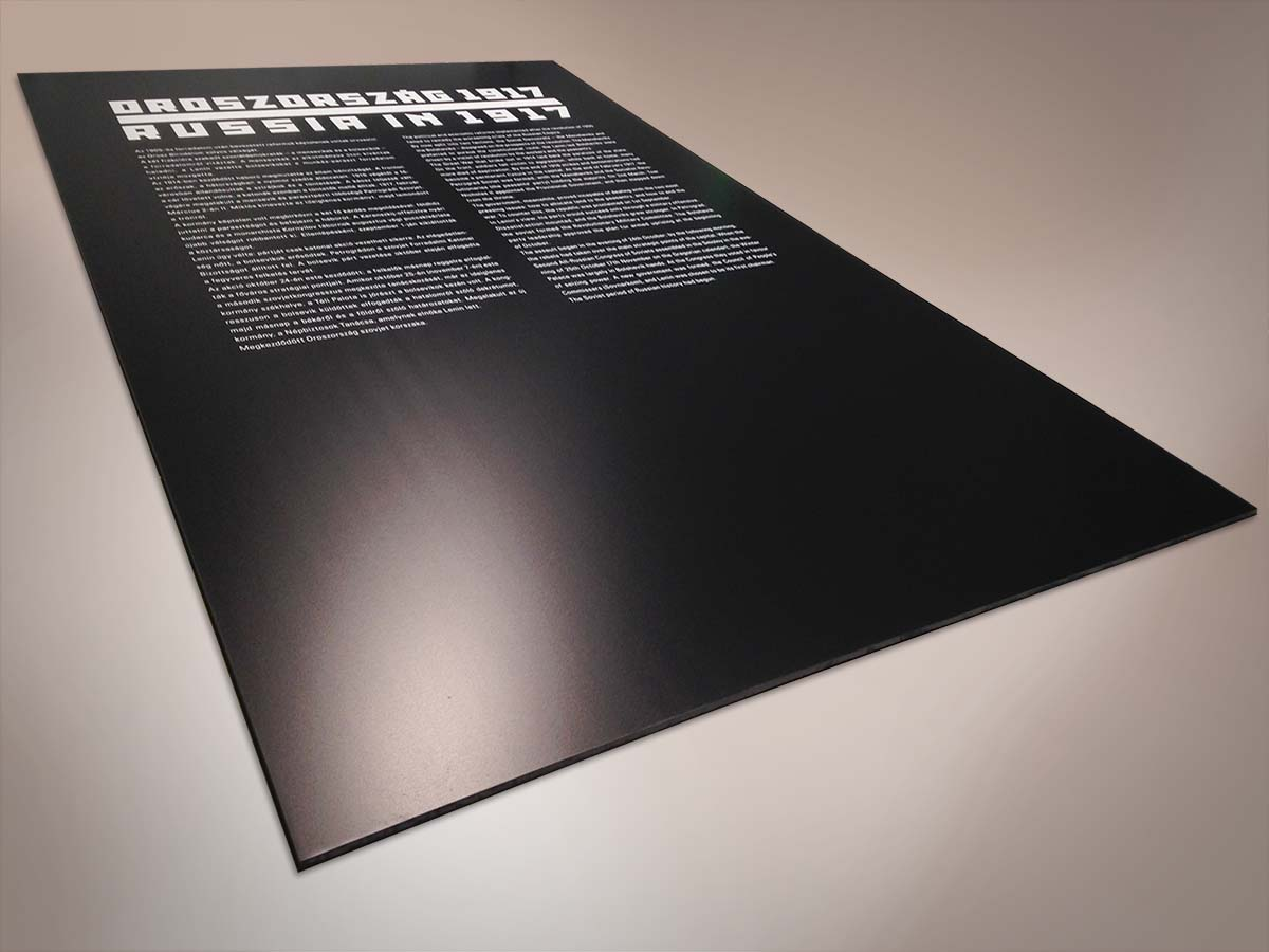 """Nagy méretű fekete tábla a tízes évek Orosz avantgárdját idéző fehér, szögletes betűs kiírással """"Oroszország 1917"""". Alatt a kiállítás fehérbetűs leírása két hasábban magyarul és angolul."""