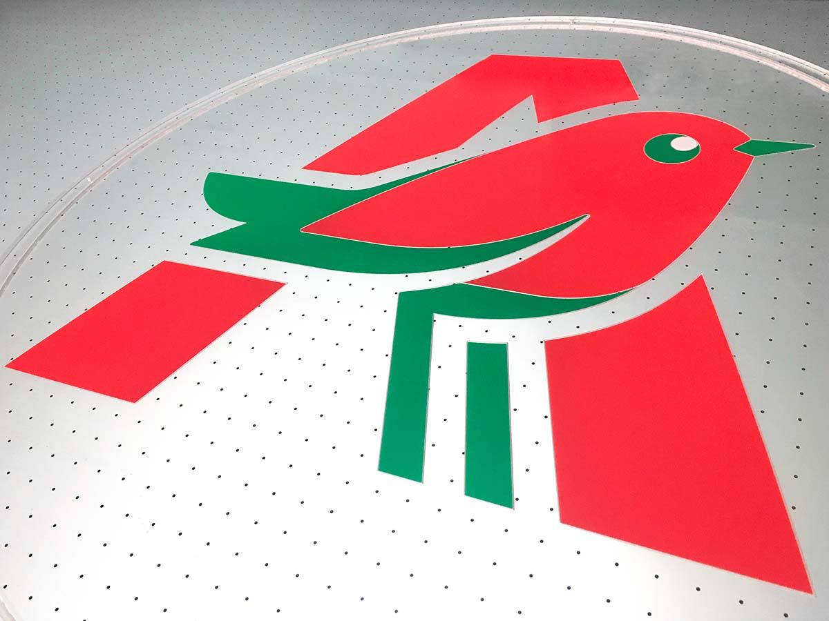 Közelkép az Auchan logójával megnyomott élvilűgító tábláról egy vákuumoasztalon, ami átlátszik az üvegszerű plexin.
