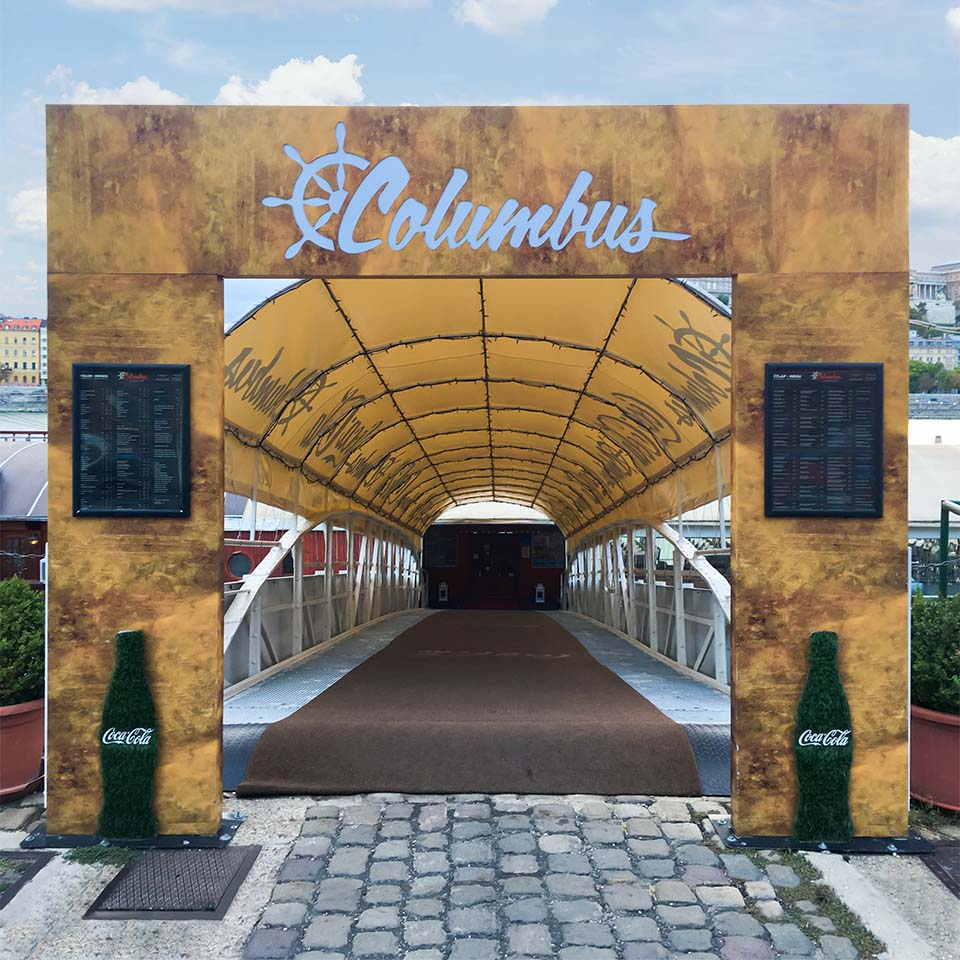 A Duna pártján álló Columbus kulisszaszerű nyomtatott kapuja, és a kivágott, hátulról átvilágítható emblémája garantáltan felhívja a figyelmet a hajóra vezető hídra és magára az étteremre.
