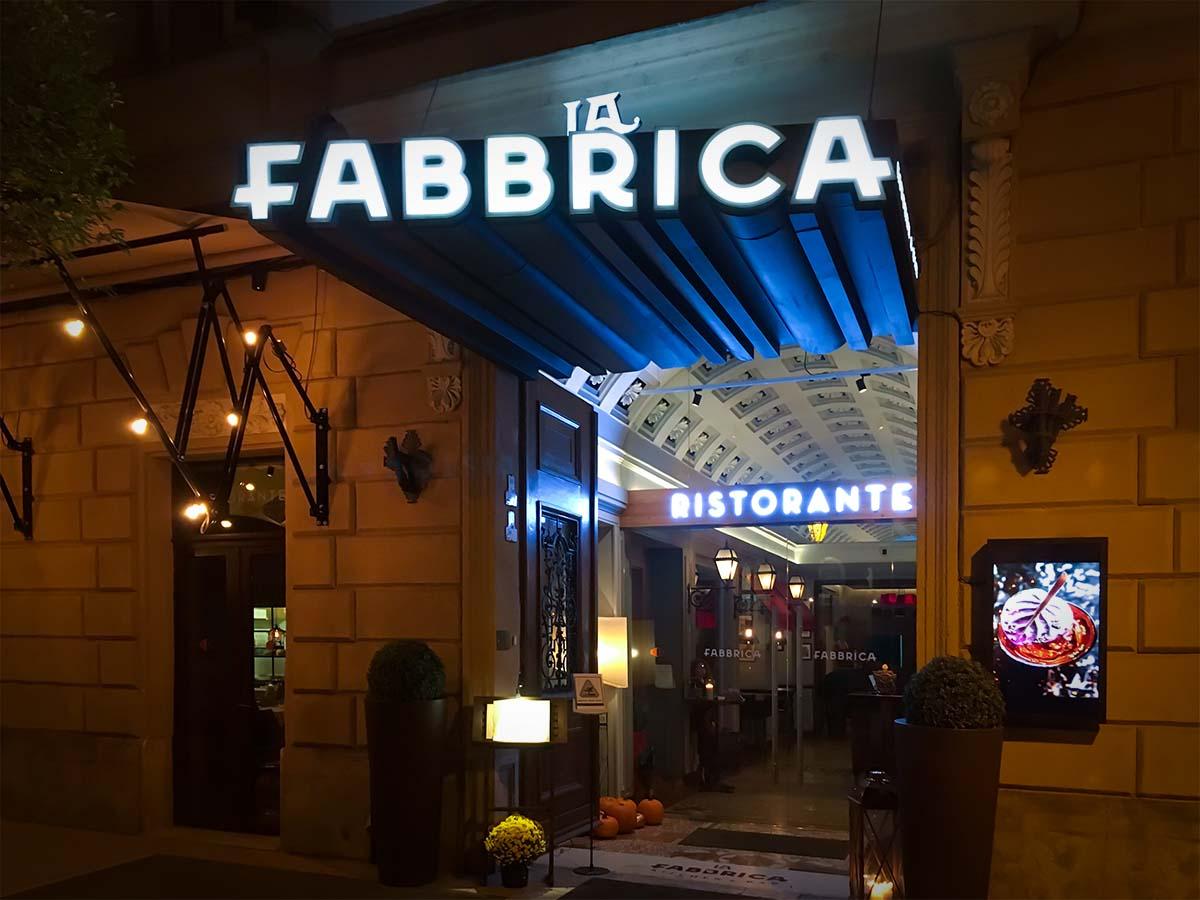 Exkluzív épületportál kékesen világító látványos La Fabbrica logóval, ami hosszan kinyúlik tetőt képezve az elegáns üvegajtós bejárat fölé.