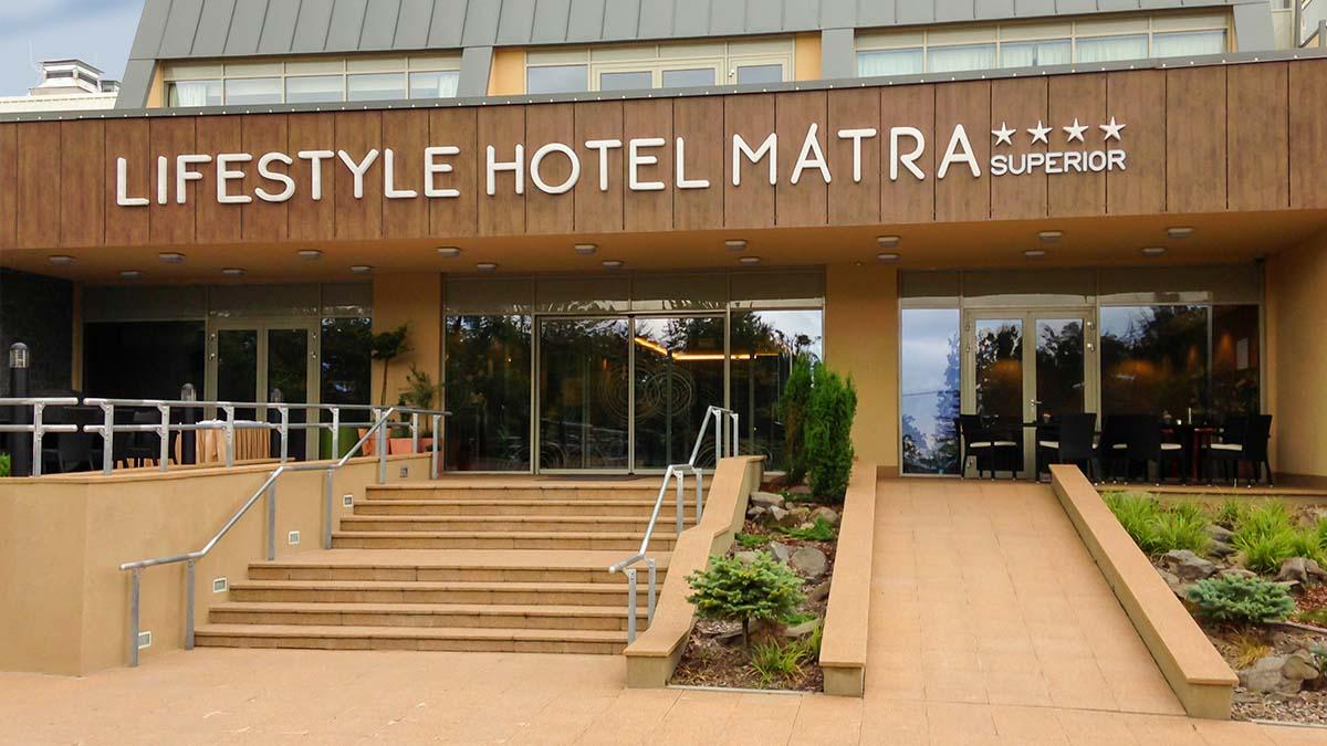 A hotel bejárata látszik a képen, ami felett függőlegesen tagolt faburkolaton a hotel nevét hirdető fehér világítófelirat van.