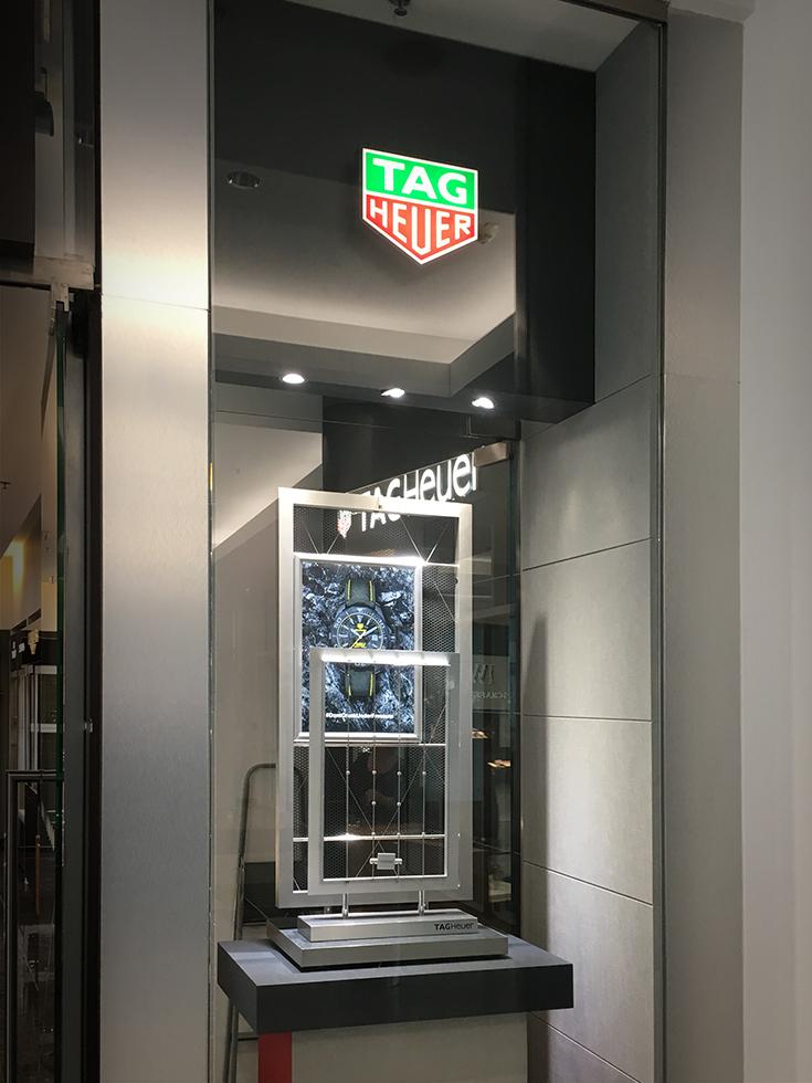 Elegáns fém-üveg kirakat, amin ott van a cég zöld-vörös élvilágítós emblémája is.