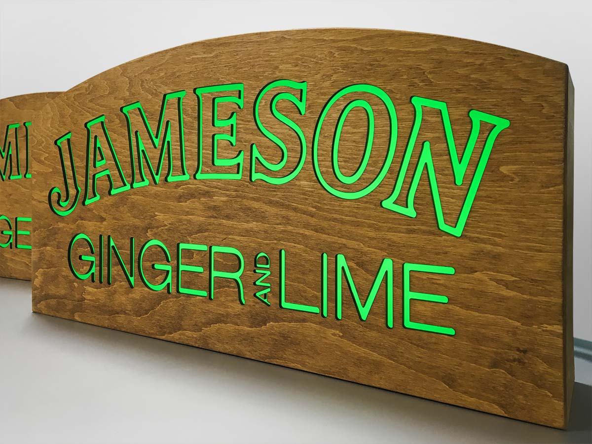 """Fából készült, belülről átvilágított, zöldesen derengő Jameson logó és """"Ginger and Lime"""" felirat."""