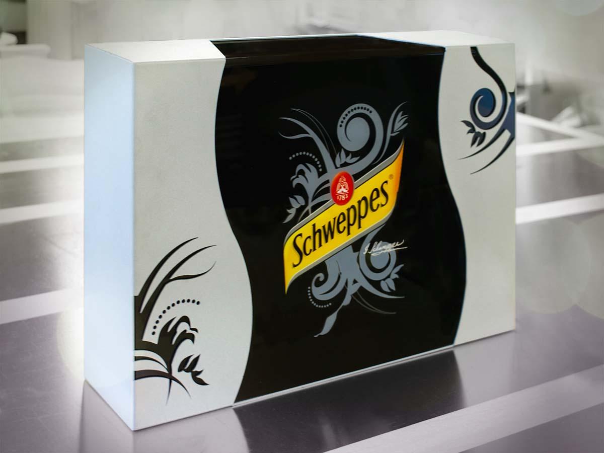 A Schweppes számára készült, finom lézervágott ornamentikákkal díszített, világító logóval ellátott fekete-fehér asztali display.