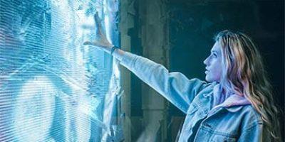 Fiatal szőkésbarna hajú lány farmerdzsekiben lenyűgözve megérint egy hatalmas világoskék fényben ragyogó LED falat.