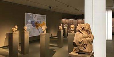 A Szépművészeti Múzeum ókor kiállítása korabeli antik szobrokkal az előtérben kellemes, fehér, világító oszlopokkal és látványos plexitérképpel a háttérben.